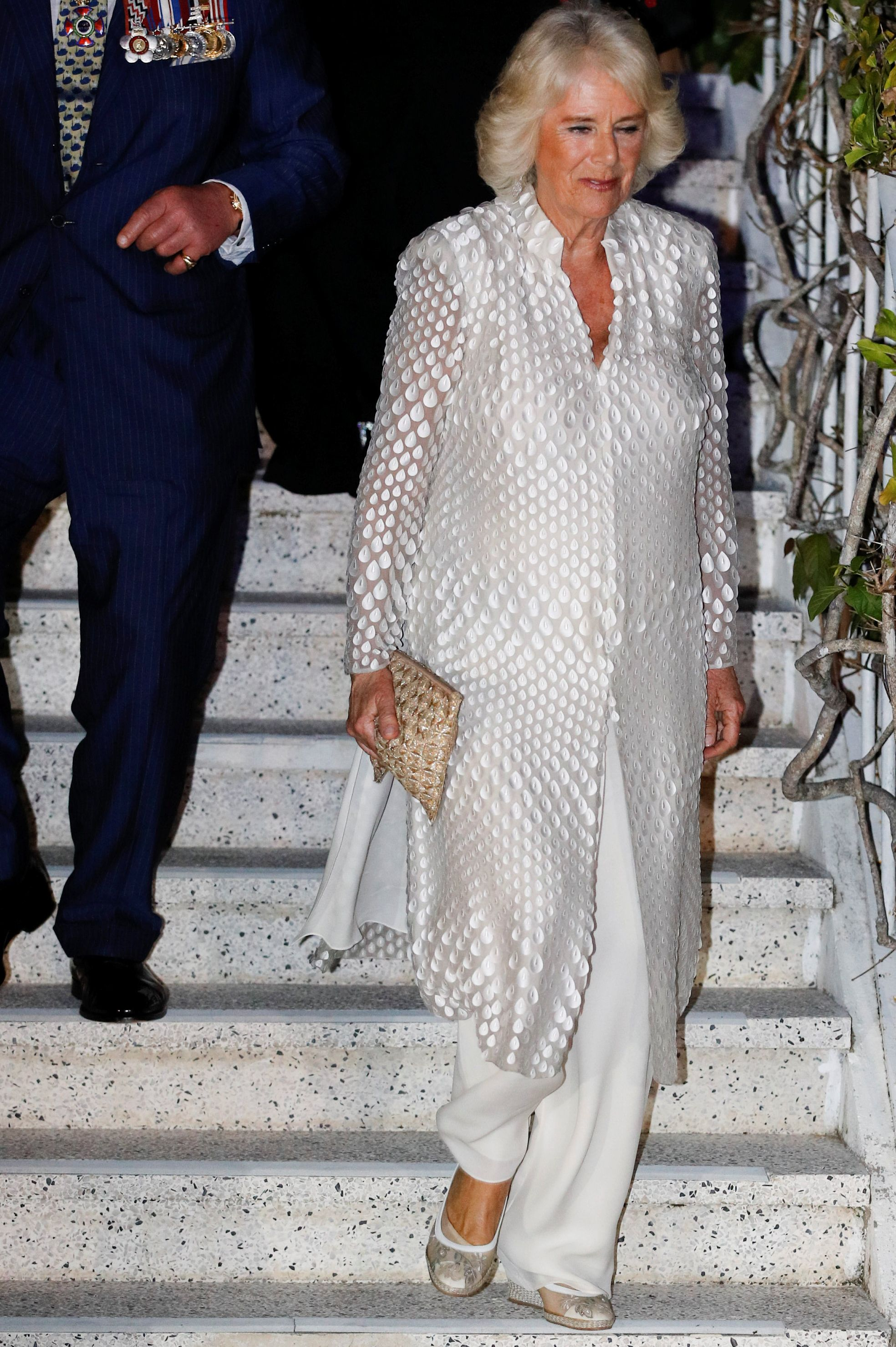 On the first night of Camilla and Charles's Caribbean tour , the Duchess paired a white sheer caftan with appliqué detailing, white wide-legged dress pants, and a wicker clutch for a dinner at Prime Minister's residence in Barbados.
