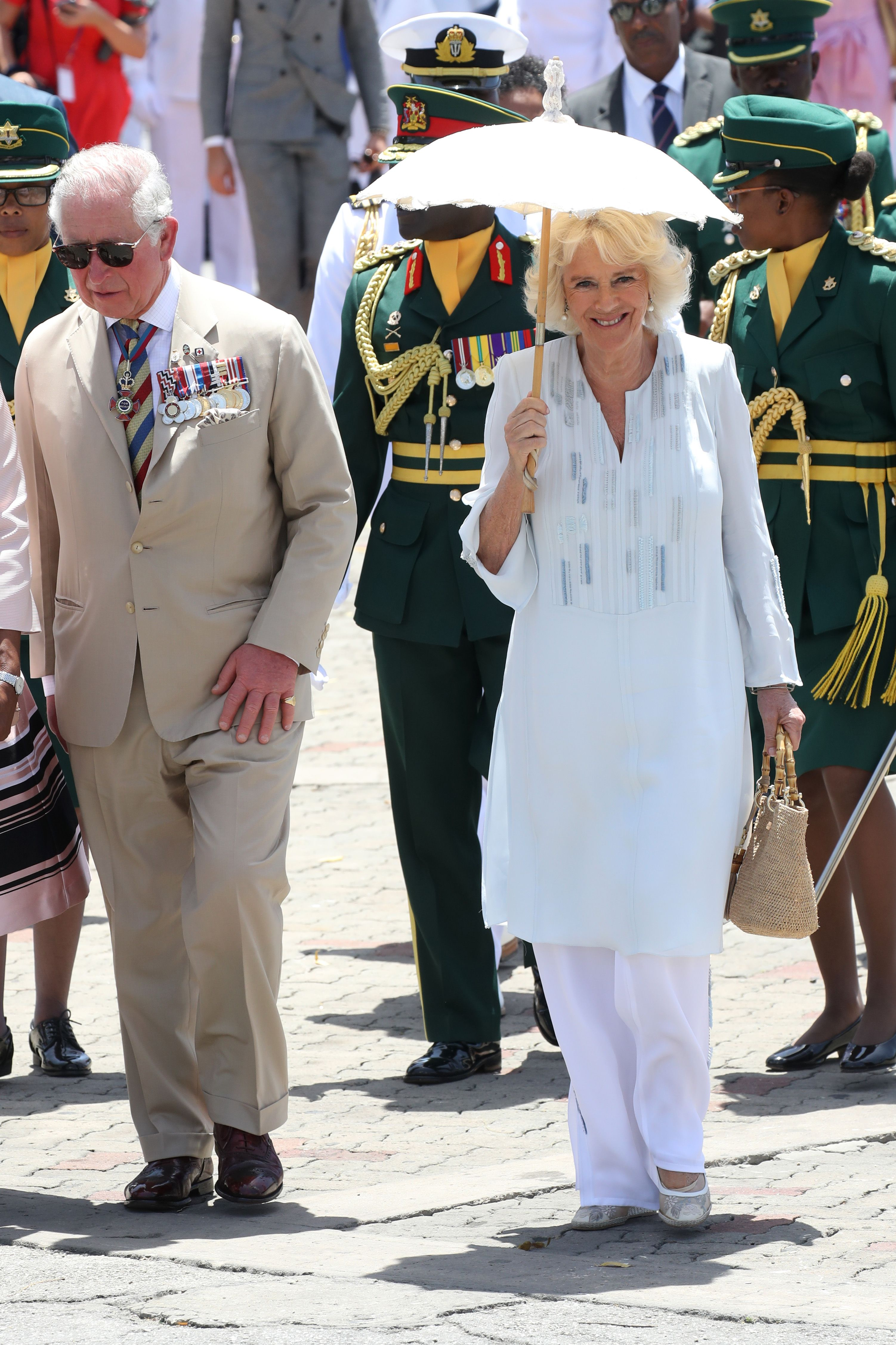 On arrival in Barbados, the Duchess of Cornwall stepped out in a light blue caftan, white pants, a straw top handle bag, and a white cloth parasol.