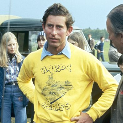 three pictures of young prince charles from left changing into an orange polo shirt, then wearing a yellow hermes jumper with jodhpurs, wearing a blue short sleeved shirt with khaki trousers