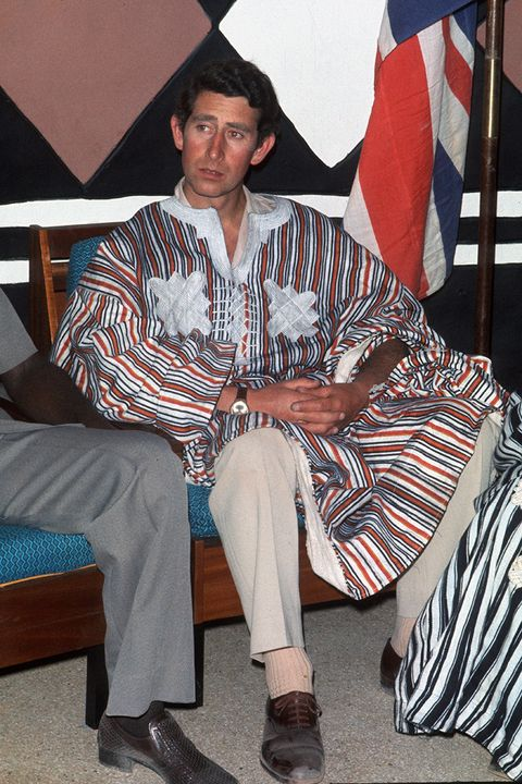 a young prince charles wearing a striped kaftan, beige slacks and beige socks and brown brogues sitting relaxing with his hands in his lap