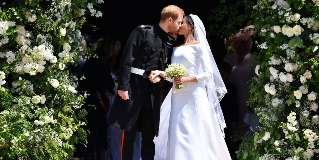 Prince Harry, Duke of Sussex kisses his wife Meghan, Duchess of Sussex as they leave from the West Door of St George's Chapel, Windsor Castle
