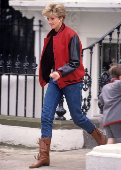 princess diana photographed in 1992 on a school run in kensington wearing blue jeans brown leather boots and a black and red varsity bomber jacket