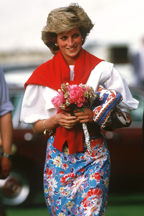 princess diana at a polo match wearing a floral skirt a white shirt with a red sweater tied around her shoulders