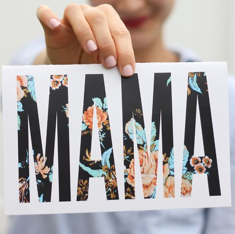 a woman holding a card in front of her that says mama