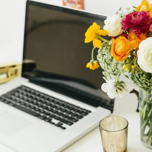 laptop and vase of flowers