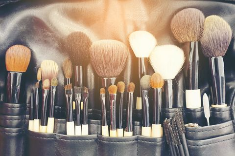 professional makeup brushes cosmetic in tube, leather bag close up brush, makeup tools of , powder, set of different objects for makeup artist in their holder set of make up products arranged
