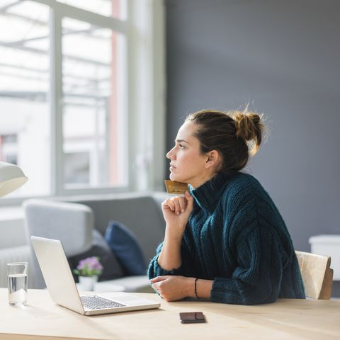 Profile of pensive woman with laptop and credit card sitting at desk at home looking out of window