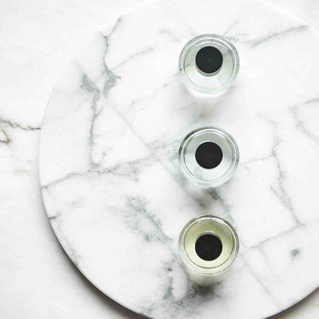 circular glass bottles on marble surface perfume bottles