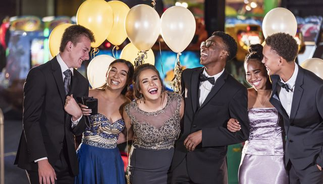 a multi ethnic group of six teenagers, three multi ethnic couples, having fun at their high school prom the two girls are wearing prom dresses and their dates are wearing a suit and tuxedo