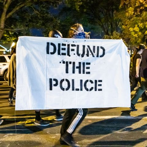 """protestor carries """"defund the police"""" sign in chicago in september 2020"""