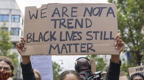 woman holding up sign reading 'we are not a trend, black lives still matter'