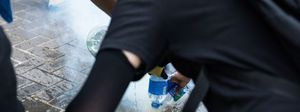 Protesters dump water on a tear gas round to extinguish it...
