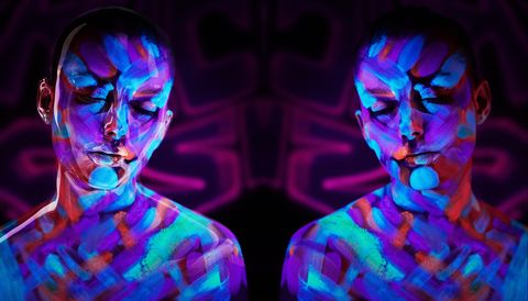 Portrait of beautiful woman with fluorescent make up in ulteaviolet light