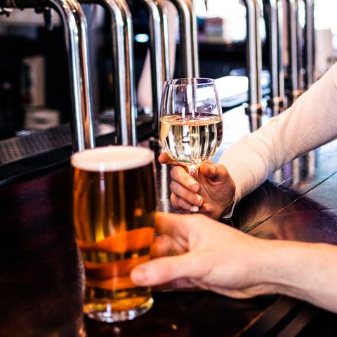 """a couple having a drink in a bar, one has a pint the other a glass of wine, to illustrate the story """"pubs might have a drink limit when they reopen after coronavirus"""""""