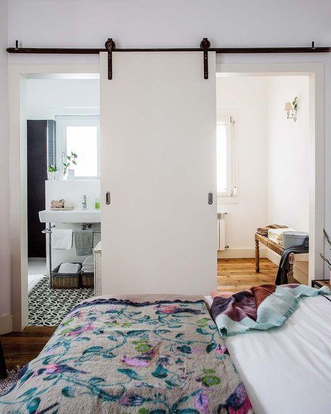 una misma puerta corredera comunica el dormitorio con el cuarto de baño y el vestidor