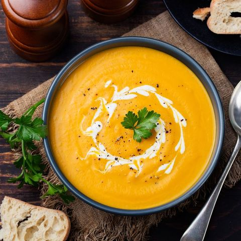 Pumpkin and carrot soup with cream and parsley Top view