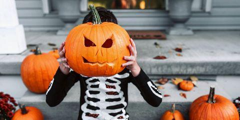 kid in skeleton costume holding up jack o lantern carved pumpkin