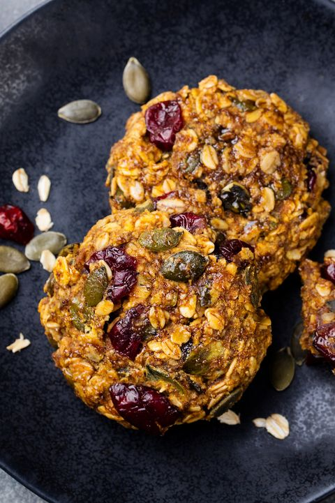 pumpkin cookies with cranberries and maple glaze on a black plate grey stone background top view