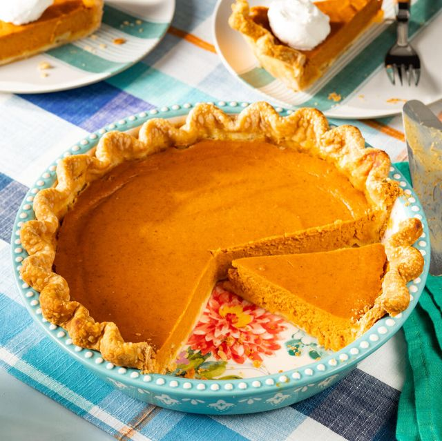 pumpkin pie recipe in a teal pie plate on a plaid table cloth with a green linen two slices of pie in the background with whipped cream