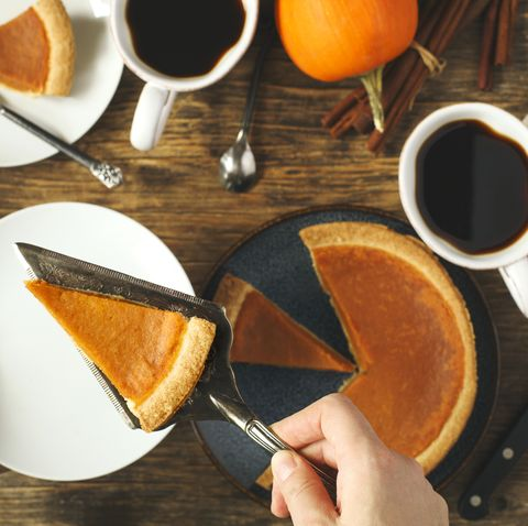 hand serving a slice of pumpkin pie with coffee cups