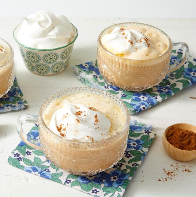 pumpkin spice latte recipe with whipped cream and pumpkin spice on blue floral napkins