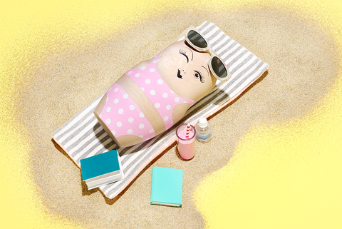 round doll lying on beach towel with smoothie