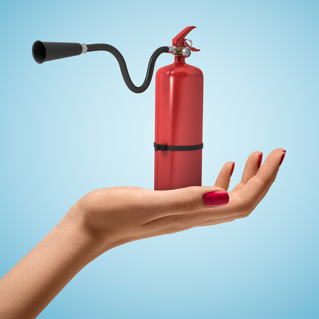 woman's hand holding tiny fire extinguisher