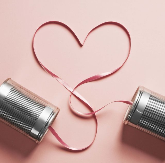 tin can telephones on a pink background with a heart shaped cord connecting them