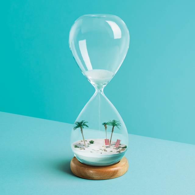 a miniature beach scene with sand, deckchairs and palm trees is recreated inside an hour glass