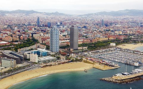 ariel view from helicopter of the shoreline and skyline of port olympic and barcelona