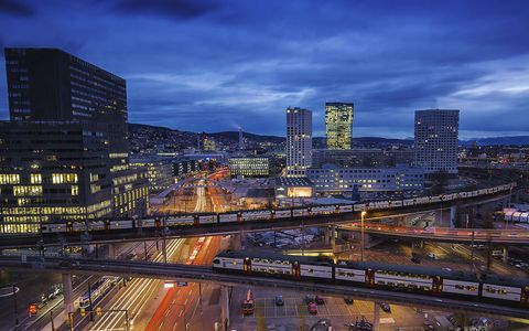 zürich cityscape at night with sbb trains passing, prime tower visible in the background on a cloudy day cars traffic light and tram visible