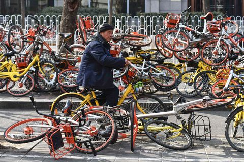 topshot   a man rides past shared bicycles piled beside a road in beijing on february 21, 2018china issued national guidelines governing bike sharing operations in 2017 in an effort to nurture a new industry credited with spurring a transport revolution while addressing mounting complaints over an accumulation of millions of bikes on city streets  afp photo  greg baker