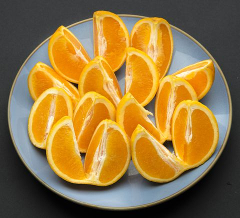 Quarter cut and unpeeled pieces of orange fruit arranged on...