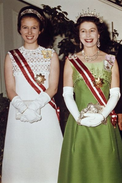 In May 1969, the monarch and her daughter, Princess Anne, went on a state visit to Austria. Both royals went full glamorous for an event at the British Embassy: Anne wore a white dress with a sash, gloves, and a tiara, while the Queen wore a lime green gown with a matching sash and lots of jewelry.
