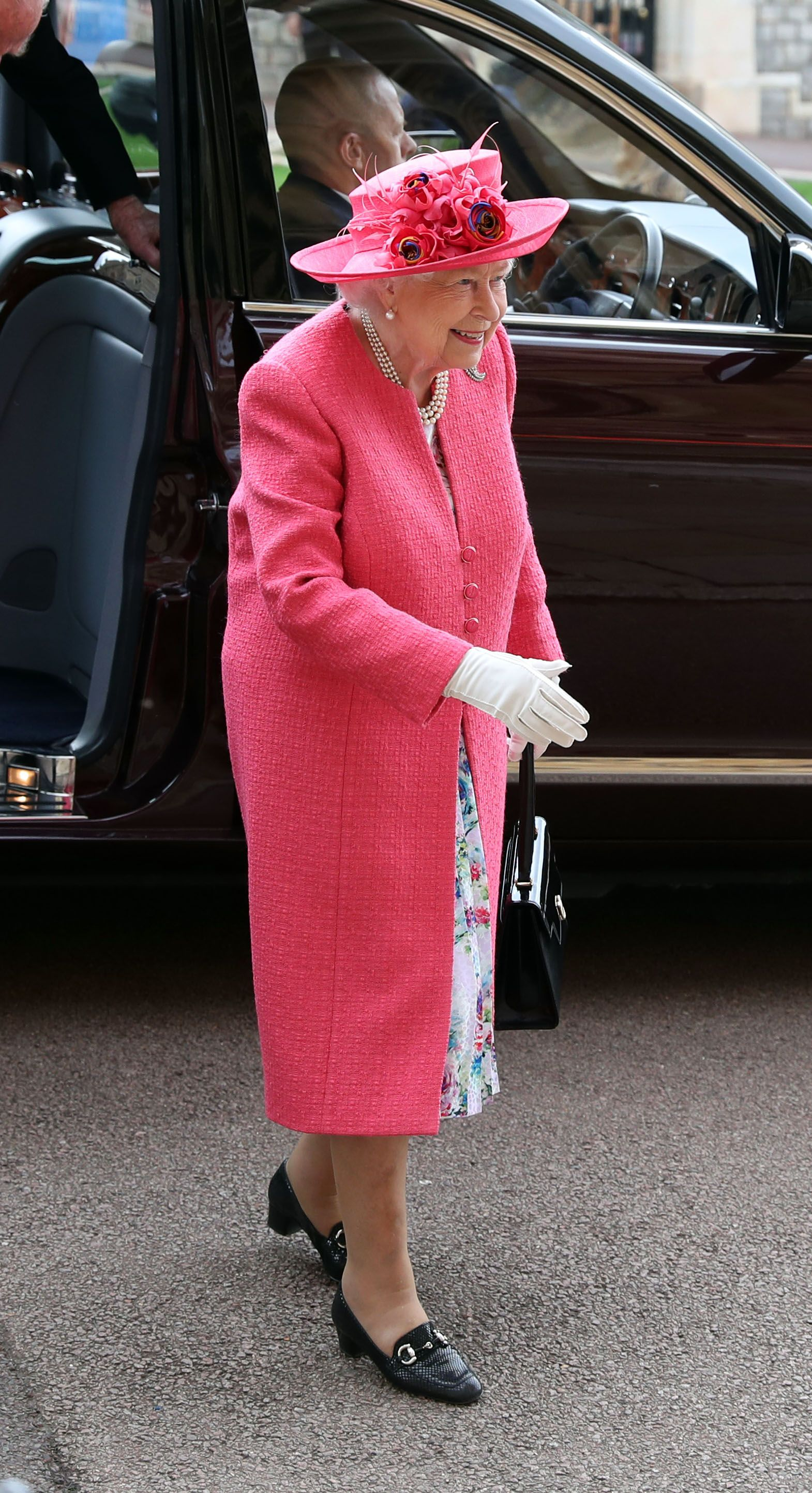In a bright pink dresscoat and hat.