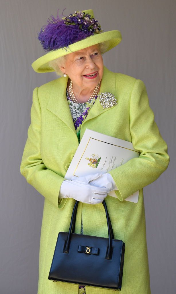 """The Queen continued showing a sunny sartorial disposition toward her grandchildren's marriages in 2018 when Prince Charles's youngest son, Prince Harry married actress Meghan Markle in a royal wedding of Cinderella proportions. Her Majesty attended the ceremony in what the palace described as """"a delicately flared dress in lime, lemon, purple and grey printed silk"""" and """"an edge to edge coat with a frogging fastening in lime silk tweed,"""" both by Stuart Parvin."""