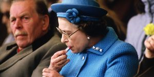 Queen Elizabeth II putting on lipstick