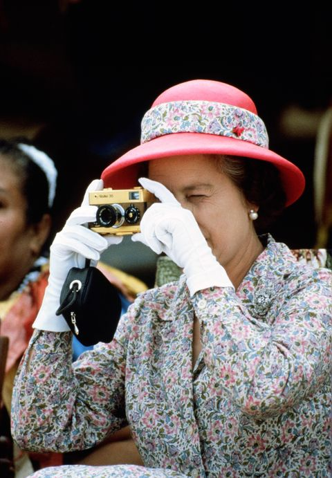 Queen Elizabeth II takes a picture with her camera whilst vi