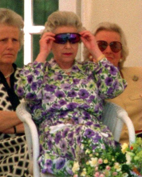queen elizabeth wears technicolour sunglasses while sitting on a chair wearing a purple floral dress