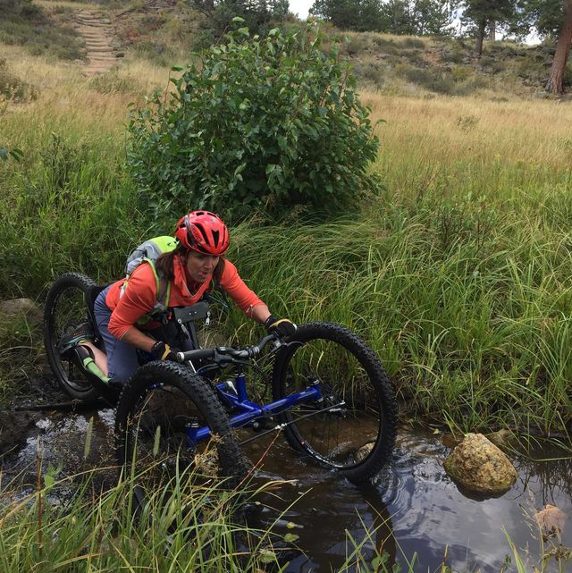 quinn brett on her adaptive cycle crossing a river