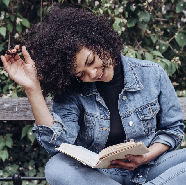 young african american woman reading a good book while chilling on bench in park