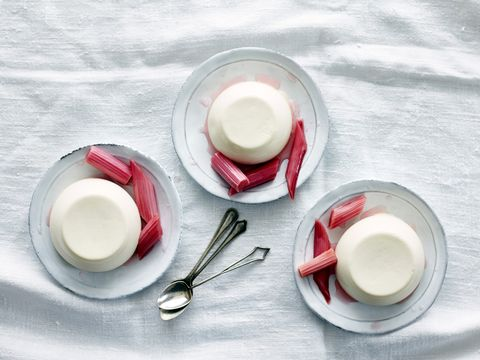 Overhead view of panna cotta desserts with rhubarb on saucers