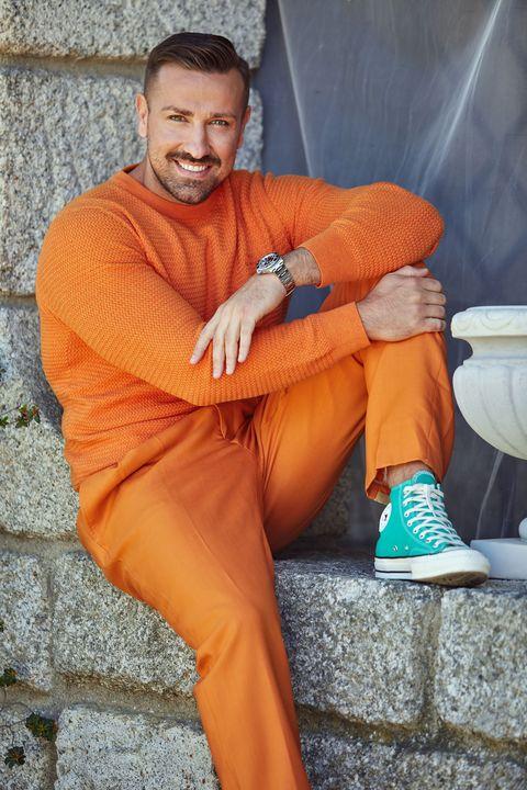 el colaborador de telecinco, con un conjunto en color naranja, sonríe a la cámara