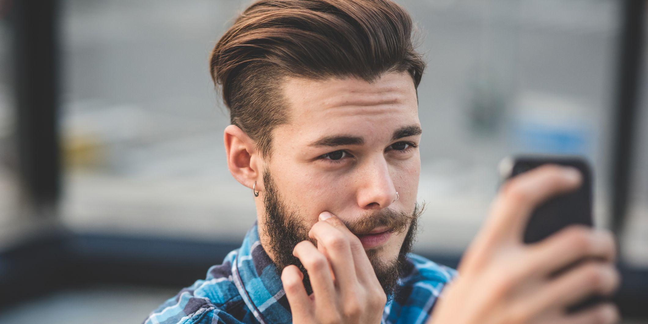 Un ragazzo si specchia con lo smartphone come un narcisista