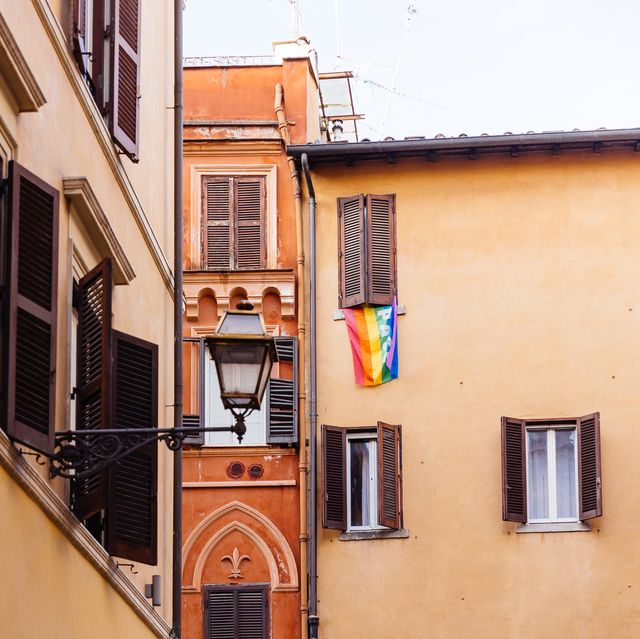 rainbow flag hanging from the window of the residential building in rome, italy