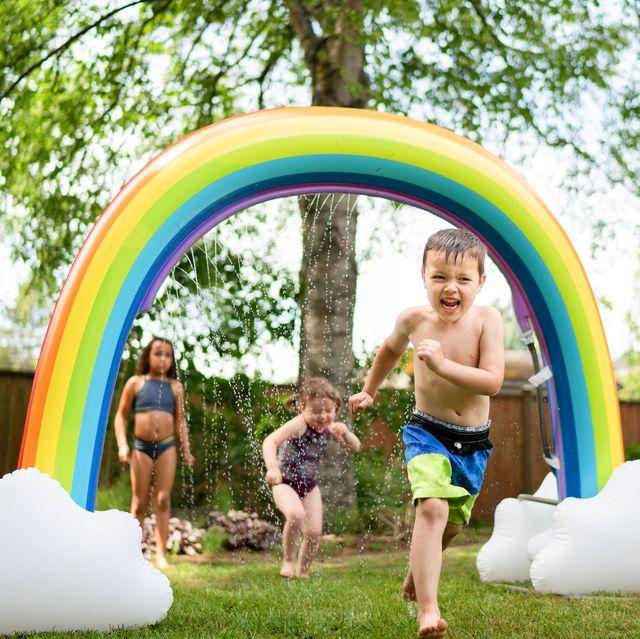 kids running through rainbow sprinkler