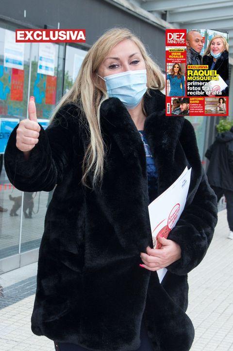 la peluquera, con mascarilla y el pulgar hacia arriba, posa para los fotógrafos tras recibir el alta en el hospital