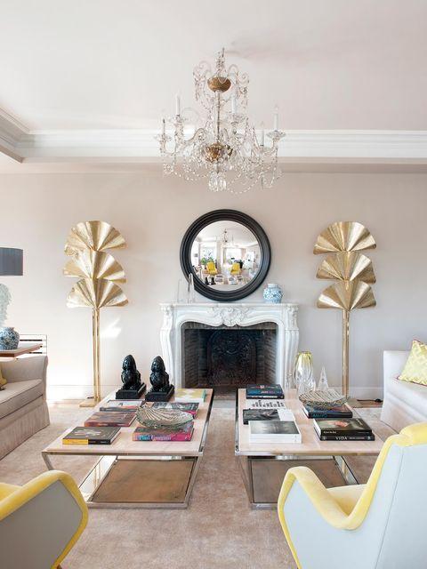 salón con chimenea de piedra clásica y decoración de estilo romántico