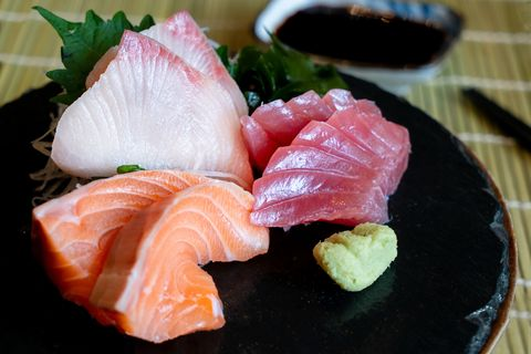 Raw fish Sashimi traditional Japanese food set includes Raw Salmon, Raw Tuna, Raw Yellow Tail (Hamachi) Sliced with sliced radish and vegetable