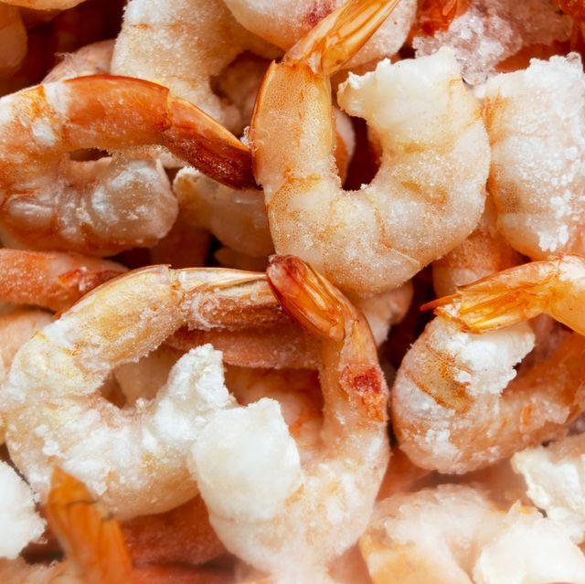 raw frozen and peeled shrimp background pile of frozen shrimps close up of frozen shrimps a lot of royal shrimp macro shot